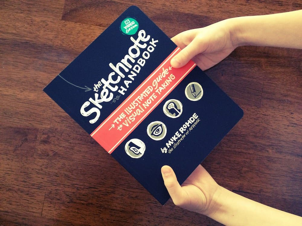 hands holding sketchnote workbook